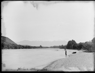 Image: Unidentified man firing a gun while standing in the shallows of the Clinton River, Southland Region