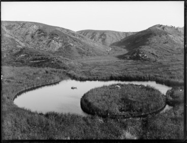Image: A lake with a circular floating island, including two men in a dinghy, Whakaki, Wairoa District