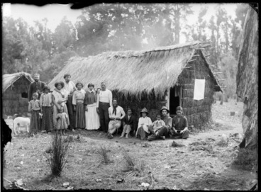 Image: Group of Maori men, women and children with William Williams and Fred Byrne outside a thatched whare, Te Kauri, Otorohanga District