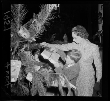Image: Little boy with his Mum attaching a Christmas present to the Christmas tree