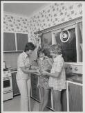 Image: Jennifer Turrall, 13 and Sally Lockyer, 14 members of the Australian swimming team in the Commonwealth Games in New Zealand in January 1974, in the kitchen with Mrs Turrall [picture].