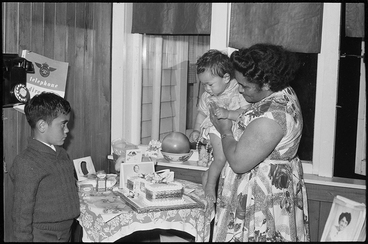 Image: Showing an unidentified Maori mother with her two children and the birthday cake at an unspecified party