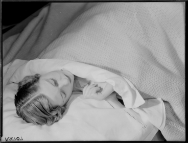 Image: Showing a model asleep in a bed advertising bed linen and blankets for Sargood Son and Ewen 1940s