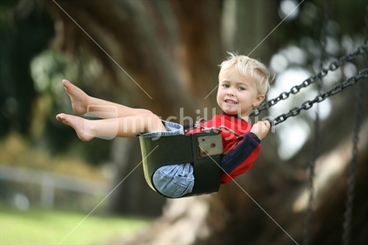 Image: a young boy enjoys a swing