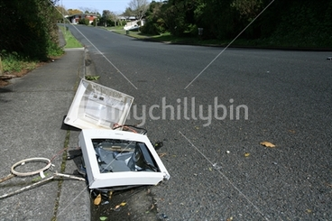 Image: The remains of a computer screen smashed in a gutter in a suburban street