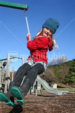 Image: School aged girl playing on a swing