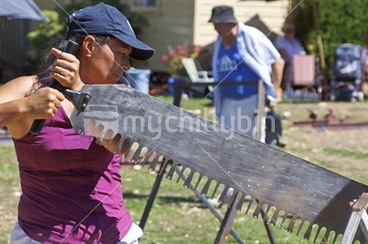 Image: Maori female competitor in the womens single handed wood sawing competition at the woodchopping events.