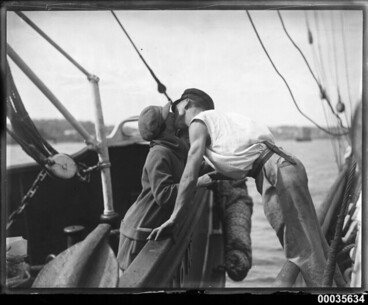 Image: Man and woman kissing across two vessels, 1920-1939