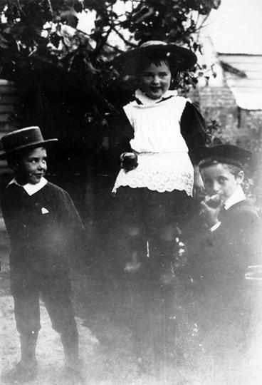 Image: Three children eating apples in the garden