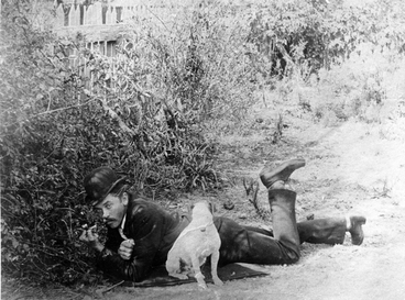 Image: A man laying on the grass with his dog