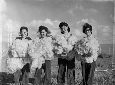 Image: [Four women in paddock holding piles of sheared wool]