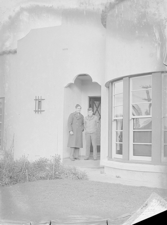 Image: [Two military servicemen pose in front of house]