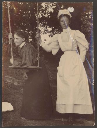 Image: [Nurse Pierce and unidentified nurse leaning/standing beside a swing]