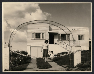 Image: [Mother and child in front of house]