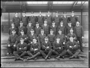 Image: Railway station unidentified workers group portrait, in uniform wearing caps with job function badges like porter or guard, under a railway station platform awning, Christchurch [Station?]