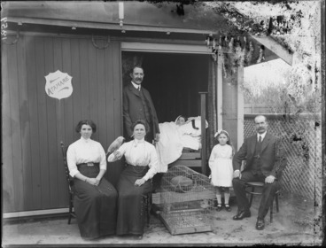 Image: Unidentified family outside house named Atamarie with parrot and cage; a woman is lying in bed inside doorway, probably Christchurch region