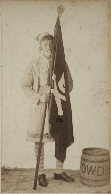 Image: Young man dressed as a pirate holding a black flag