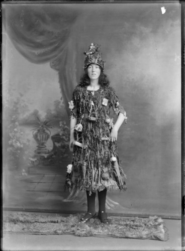 Image: Studio portrait of unidentified young woman in Christmas tree fancy dress and hat costume, with little presents and decorations hanging off her, Christchurch