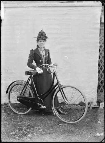 Image: Unidentified young woman, with a bicycle, outdoors, with a backdrop, probably Christchurch district