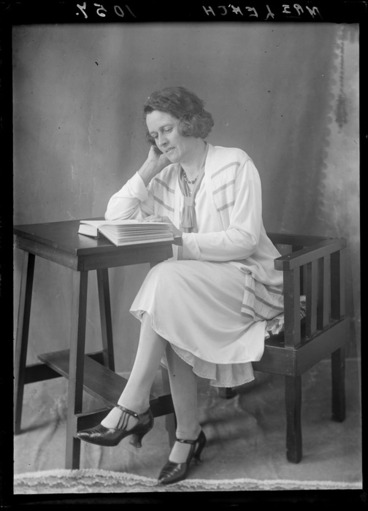 Image: Mrs Leach from Hastings reading a book seated at a small table