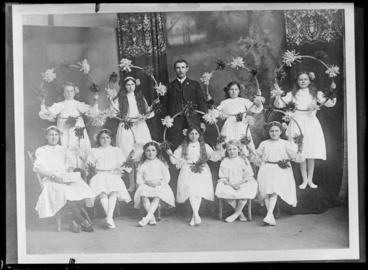 Image: Studio portrait of unidentified ten young girls wearing hair ribbons and holding hula hoops decorated with small pompoms, standing with a man with a moustache, Christchurch