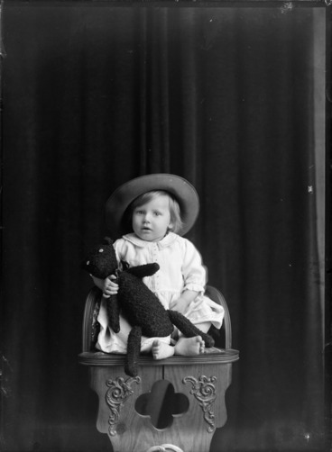 Image: Studio family portrait of unidentified young girl with large hat and holding a teddy bear while sitting on wooden high chair, Christchurch