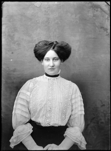 Image: Studio portrait of an unidentified woman, wearing a high-necked lace blouse and a pompadour hairstyle, possibly Christchurch district