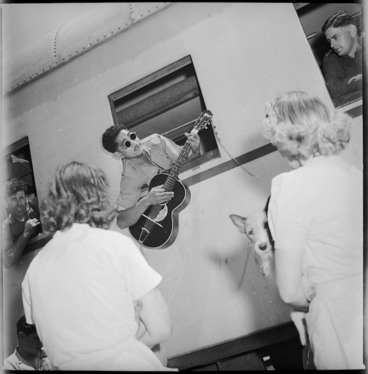 Image: Blind Maori soldier repatriated from Italy playing guitar out of railway carriage window at Alexandria, World War II - Photograph taken by G R Bull