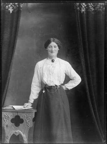 Image: Studio unidentified portrait of a woman in a lace shoulder cotton shirt with a large circular neck brooch, dark skirt and neck chain pendant, standing with a wooden highchair and book, Christchurch