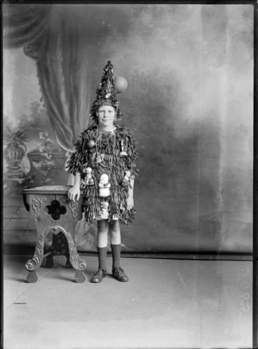 Image: Studio portrait of unidentified girl dressed as Christmas tree with ornaments, probably Christchurch