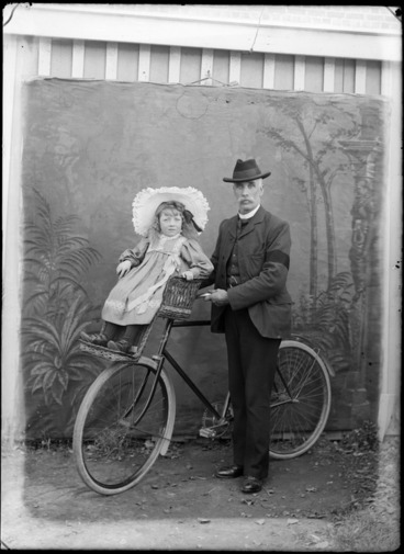 Image: Outdoors portrait of man holding a bicycle and a young girl with large hat is on a front handlebars wicker child carrier, probably Christchurch region