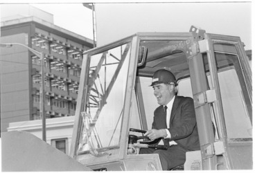 Image: Justice Minister Geoffrey Palmer driving a front end loader on the construction site of the new Wellington District Court - Photograph taken by Merv Griffiths