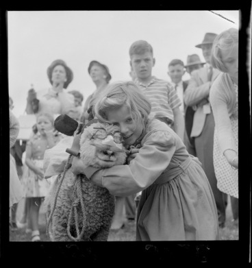 Image: Unidentified young girl with her winning pet lamb, which is wearing novelty glasses with nose and moustache, Palmerston North Agricultural & Pastoral Show (A & P Show), Manawatu-Whanganui Region