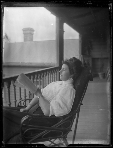 Image: Unidentified woman sitting in a chair reading a book