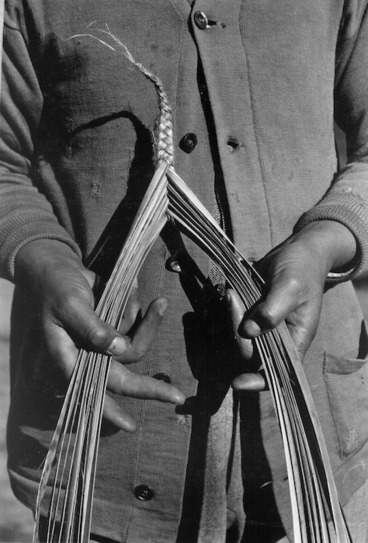 Image: Photograph of a person demonstrating the plaiting and weaving of flax