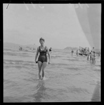 Image: An unidentified young woman who just completed the Somes Island Petone swim on Petone Beach with children looking on, Wellington City