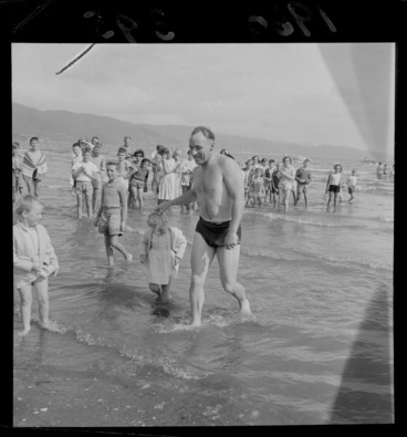 Image: An unidentified man completing the Somes Island Petone swim being greeted on Petone Beach by his young daughters with children looking on, Wellington City