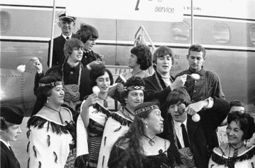 Image: The Beatles and an unidentified Maori group at Wellington Airport during their New Zealand tour