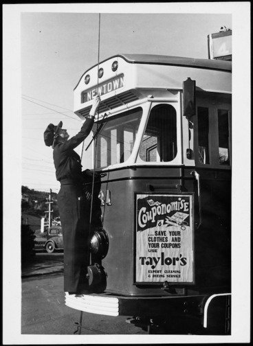 Image: Woman conductor placing the tram pole on the wire