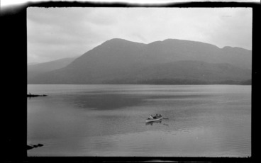 Image: Lake scene, including people in row boat on lake with mountain in background, Killarney, County Kerry, Ireland