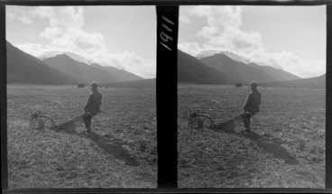Image: An unidentified man with plough in a field, haystack in distance and mountains beyond, probably West Coast Region