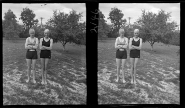 Image: Two unidentified girls wearing swimsuits and bathing caps, standing on grass, location unidentified