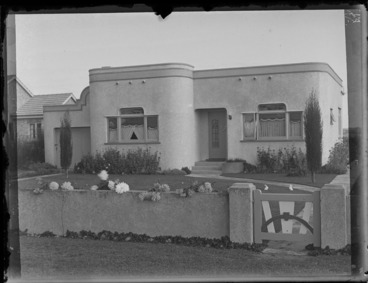 Image: Exterior of an art deco house with rabbit sculptures on the front lawn and dahlias in the garden, location unidentified