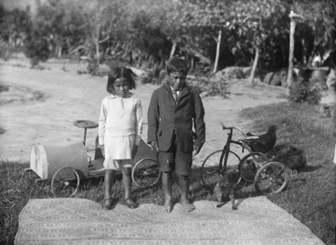 Image: Maori girl and boy alongside a whariki, peddle-cart and tricycle