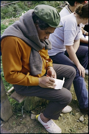 Image: Poet Hone Tuwhare writing in his notepad during a stop on the Maori Land March