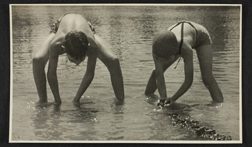 Image: Two children wearing swimming costumes in shallows