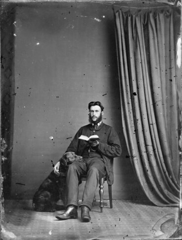 Image: Unidentified man, seated, with a book and his dog