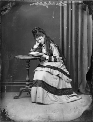 Image: Young woman [from Wargan family] looking at photograph album