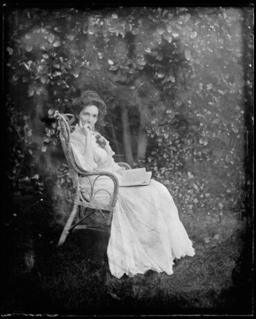 Image: Woman seated in cane chair outdoors