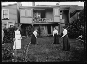 Image: Four women playing croquet in the backyard of a house